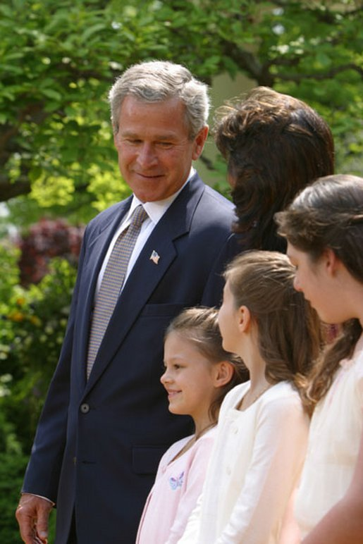 President George W. Bush looks toward Lacy Lyons, center, before signing the S. 151, PROTECT Act of 2003, in the Rose Garden Wednesday, April 30, 2003. Abducted by their father, Lacy, 10, and her sister Nyoka, 8, left, were found after an AMBER alert was activated throughout the state of Florida. White House photo by Paul Morse