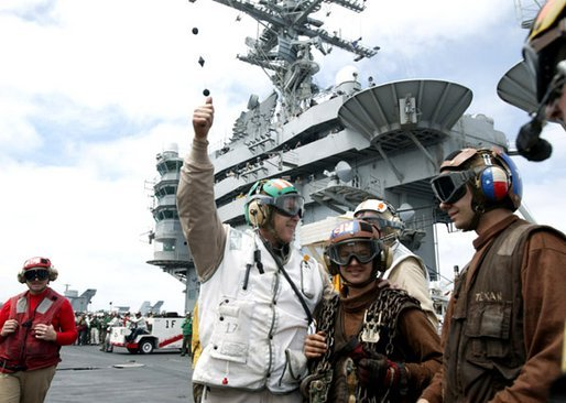 After a successful landing, President George W. Bush gives the thumbs-up sign as he meets with flight crews on the deck of the USS Abraham Lincoln Thursday, May 1, 2003. White House photo by Paul Morse