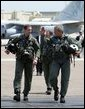 President George W. Bush walks across the tarmac with NFO Lt. Ryan Phillips to Navy One, an S-3B Viking jet, at Naval Air Station North Island in San Diego Thursday, May 1, 2003. Flying to the USS Abraham Lincoln, the President will address the nation and spend the night aboard ship. White House photo by Susan Sterner.
