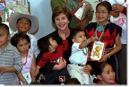 Children at the Kayenta Indian Health Service Clinic crowd around Laura Bush after she reads to them and tours the facility in Kayenta, Arizona, May 8, 2003.  White House photo by Susan Sterner
