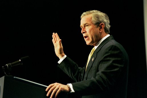 Recalling the experience of watching a Mexican-born Marine take America's oath of citizenship, President George W. Bush raises his right hand as he addresses the National Hispanic Prayer Breakfast in Washington, D.C., Thursday, May 15, 2003. White House photo by Eric Draper
