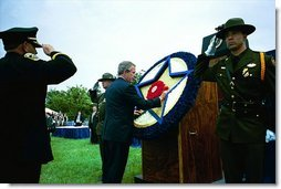 President George W. Bush places a flower on a memorial wreath during the Annual Peace Officers Memorial Service at the U.S. Capitol Washington, D.C., Thursday, May 15, 2003.  White House photo by Paul Morse