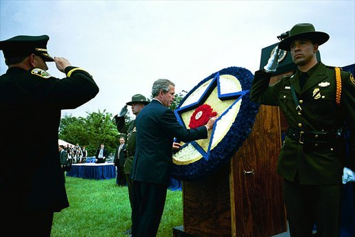 President George W. Bush places a flower on a memorial wreath during the Annual Peace Officers' Memorial Service at the U.S. Capitol Washington, D.C., Thursday, May 15, 2003. White House photo by Paul Morse.