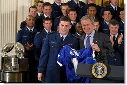 "President George W. Bush receives a jersey during the presentation of the Commander-in-Chief's Trophy in the East Room Friday, May 16, 2003. ""I'm proud to welcome back to the White House the Air Force Academy Falcons, who have now won the Commander-in-Chief's Trophy for their six consecutive year, and 16th time overall,"" said the President in his remarks.  White House photo by Paul Morse"