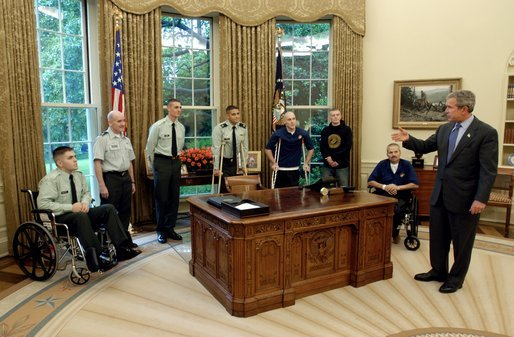 President George W. Bush talks with soldiers after taping his weekly radio address in the Oval Office Friday, May 16, 2003. Honoring Armed Forces Day on May 17th, the President invited soldiers to attend the recording of the address. White House photo by Eric Draper