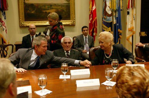 President George W. Bush reaches out to comfort Isabel Roque during a roundtable discussion with Cuban dissidents in the Roosevelt Room at the White House Tuesday, May 20, 2003. Ms. Roque spoke of family members currently imprisoned in Cuba. White House photo by Susan Sterner.
