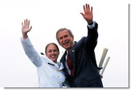 After receiving her degree from President George W. Bush, a cadet and the President wave to the gathered crowd during the United States Coast Guard Academy Commencement in New London, Conn., Wednesday, May 21, 2003.  White House photo by Eric Draper