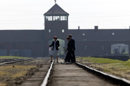 President Bush and Mrs. Bush are escorted across railroad tracks during a tour of the Birkenau concentration camp in Poland by Auschwitz Museum Senior Curator Dr. Teresa Swiebocka, Saturday, May 31, 2003. White House photo by Paul Morse