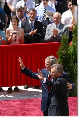 President George W. Bush and President of Poland Aleksander Kwasniewski acknowledge the audience following their speeches in the court yard of the Wawel Royal Palace in Krawkow, Poland, Saturday, May 31, 2003.  White House photo by Paul Morse