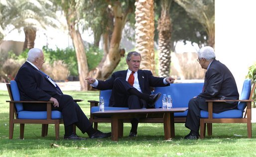 President George W. Bush, center, discusses the Middle East peace process with Prime Minister Ariel Sharon of Israel, left, and Palestinian Prime Minister Mahmoud Abbas in Aqaba, Jordan, Wednesday, June 4, 2003. White House photo by Paul Morse