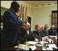 President George W. Bush listens to Robert Sutton, left, a graduate of the Prison Fellowship Ministries InnerChange Freedom Initiative, during a roundtable discussion in the Roosevelt Room Wednesday, June 18, 2003. The initiative is is part of the Texas Department of Criminal Justice System and the new prisoner reentry and treatment program proposed by the Department of Justice.   White House photo by Tina Hager