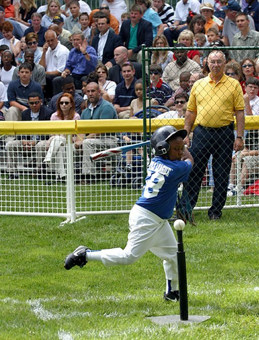 A little leaguer winds up for a big hit during the first game of the 2003 season of White House South Lawn Tee Ball Sunday, June 22, 2003. White House photo by Lynden Steele.