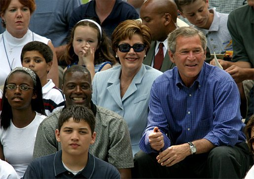 President George W. Bush, Laura Bush and Washington Redskins star Darrell Green (seated in front of Mrs. Bush) watch the tee ball action on the South Lawn Sunday, June 22, 2003. Mr. Green is the Chairman of the President's Council on Service and Civic Participation and during the game recognized Tanisha Faulkner and Mileika Miki of Fort Meade 4-H for their volunteer service. White House photo by Lynden Steele.