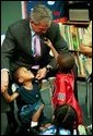 During a tour of Highland Park Elementary School in Landover, Md., President George W. Bush plays with children at the school's Head Start Center where he discussed strengthening America's Head Start Program Monday, July 7, 2003.  White House photo by Paul Morse