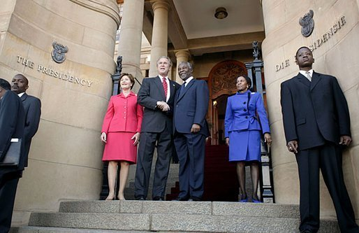 President George W. Bush and Laura Bush are welcomed to the Union House in Pretoria, South Africa, by South African President Thabo Mbeki and Zanele Mbeki Wednesday, July 9, 2003. White House photo by Paul Morse