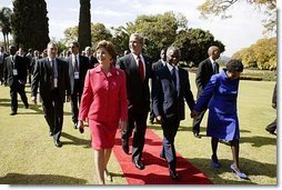 Presidents Bush and Mbeki walk together with Mrs. Bush and Mrs. Mbeki after speaking to the media at the Guest House in Pretoria, South Africa, Wednesday, July 9, 2003.  White House photo by Paul Morse