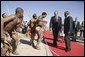 Walking with President Festus Gontebanye Mogae of Botswana, President George W. Bush and Laura Bush (not pictured) are greeted by traditional dancers upon their arrival at Sir Seretse Khama International Airport Thursday, July 10, 2003.