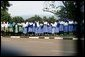 School children watch as the Presidential motorcade passes through Entebee, Uganda, July 11, 2003. White House photo by Paul Morse.