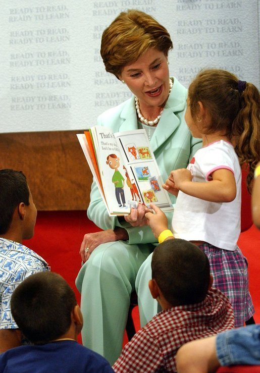 "Laura Bush reads the book ""That's My Dog"" to students from the Clayton Center, a migrant Head Start Program, at the Raleigh Durham Airport in Raleigh, N.C. Friday, July 18, 2003. Mrs. Bush presented each child a book to help encourage reading and school readiness. White House photo by Tina Hager"