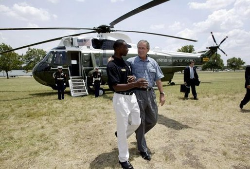 President George W. Bush walks with YMCA volunteer Andrew Simpson after arriving on Marine One in Dallas, Texas, Friday, July 18, 2003. White House photo by Paul Morse.