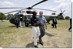President George W. Bush walks with YMCA volunteer Andrew Simpson after arriving on Marine One in Dallas, Texas, Friday, July 18, 2003.  White House photo by Paul Morse