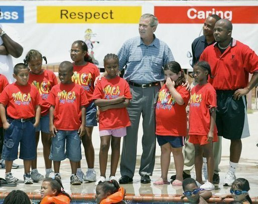 President George W. Bush views swimming pool activities of children during a tour of Lakewest Family YMCA in Dallas, Texas, Friday, July 18, 2003. White House photo by Eric Draper