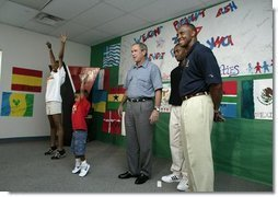 President George W. Bush watches an exercise class during a tour of Lakewest Family YMCA in Dallas, Texas, Friday, July 18, 2003. Also pictured, at far right, are Lynn Swann, Chairman of the President's Council on Physical Fitness and Sports and YMCA Volunteer Andrews Simpson.  White House photo by Paul Morse