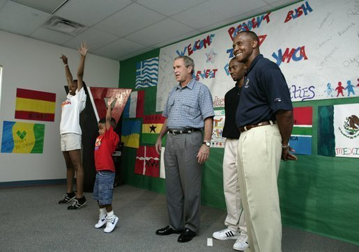 President George W. Bush watches an exercise class during a tour of Lakewest Family YMCA in Dallas, Texas, Friday, July 18, 2003. Also pictured, at far right, are Lynn Swann, Chairman of the PresidentÕs Council on Physical Fitness and Sports and YMCA Volunteer Andrews Simpson. White House photo by Paul Morse