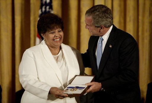 Vera Clemente accepts the Presidential Medal of Freedom from President George W. Bush on behalf of her husband Roberto Clemente Walker during a ceremony in the East Room Wednesday, July 23, 2003. A Hall of Fame baseball player, Mr. Clemente was committed to helping the less fortunate. The medal is the highest civilian award. White House photo by Paul Morse