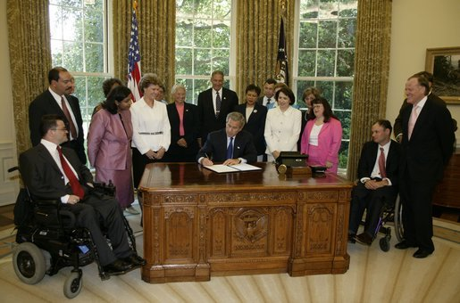 In honor of the 13th anniversary (July 26, 2003) of the Americans with Disabilities Act, President George W. Bush signs the executive order renaming the President's Committee on Mental Retardation to the President's Committee for People with Intellectual Disabilities (PCPID) in the Oval Office Friday, July 25, 2003. In addition to witnessing the signing, the PCPID were on hand to hear President Bush record his weekly radio address. White House photo by Paul Morse.