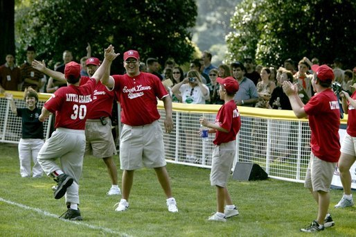 Coaches cheer their fellow teammate after he hit a home-run ball out of the park during a game in the White House South Lawn Tee-Ball League Sunday, July 27, 2003. White House photo by Lynden Steele.