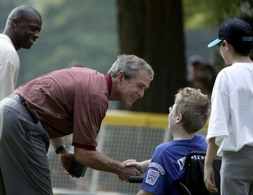 After a game of cheers and close calls, President George W. Bush and Washington Redskin star Darrel Green greet each player with handshakes and an autographed baseball during a ceremony for the White House South Lawn Tee-Ball League Sunday, July 27, 2003. White House photo by Lynden Steele.