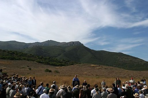 As hills in the Santa Monica Mountains National Recreation Area roll through the landscape, President George W. Bush delivers remarks with Secretary of the Interior Gale Norton in Thousand Oaks, Calif., August 15, 2003. White House photo by Paul Morse.