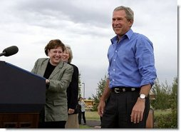 President George W. Bush is introduced by Secretary of Agriculture Ann Veneman before discussing his healthy forest initiative in Redmond, Ore., Thursday, August 21, 2003. Secretary of the interior Gale Norton is pictured in the background.  White House photo by Paul Morse