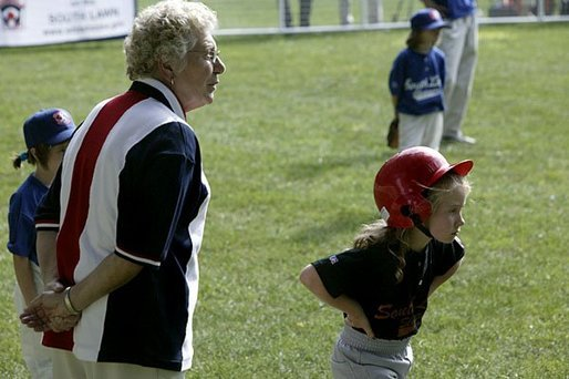 A runner with the Hamilton Little Lads of Hamilton, N.J., waits to make her next move with her honorary base coach Dolly White, former fielder with the Fort Wayne Daises and the Kenosha Comets, during the last game of the 2003 White House South Lawn Tee Ball season Sunday, Sept. 7, 2003. Ms. White played professional baseball with the All-American Girls Professional Baseball League Players Association, which operated from 1943 to 1954. White House photo by Lynden Steele.