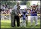 President George W. Bush and Honorary Commissioner Cal Ripken present a little leaguer with a warm congratulations and an autographed baseball after playing the last game of the 2003 White House South Lawn Tee Ball season Sunday, Sept. 7, 2003. White House photo by Lynden Steele.