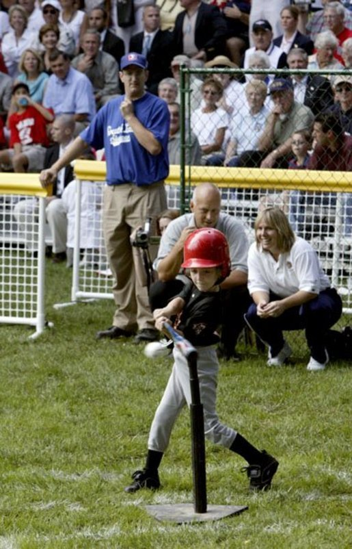 A little slugger from Kalamazoo, Mich., takes his hit under the expert gaze of Honorary Commissioner and Baltimore Orioles great Cal Ripken and Olympic Gold Medalist and Honorary Third Base Coach Dot Richardson during the last game of the White House South Lawn Tee Ball season Sunday, Sept. 7, 2003. White House photo by Lynden Steele.