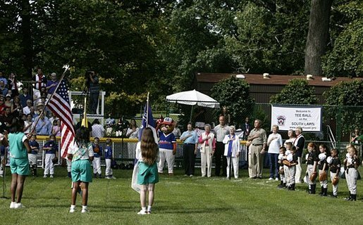 President George W. Bush stands for the singing of the national anthem with representatives of the All-American Girls Professional Baseball League Players Association during the opening ceremony for the last game of the 2003 White House South Lawn Tee Ball season Sunday, Sept. 7, 2003. The AAGPBL gave more than 600 woman the opportunity to play professional baseball from 1943 to 1954. White House photo by Lynden Steele.
