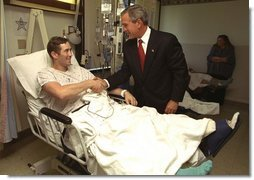 President George W. Bush shakes hands with Staff Sgt. Ethan Craig of Chester, Mass., after awarding him The Purple Heart at Walter Reed Army Medical Center Thursday, Sept. 11, 2003. Visiting with patients who were injured while serving in Operation Iraqi Freedom, President Bush awarded 11 Purple Hearts.  White House photo by Paul Morse