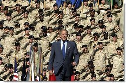 President George W. Bush walks on stage before addressing military personnel and their families at Ft. Stewart, Ga., Friday, Sept. 12, 2003.  White House photo by Paul Morse