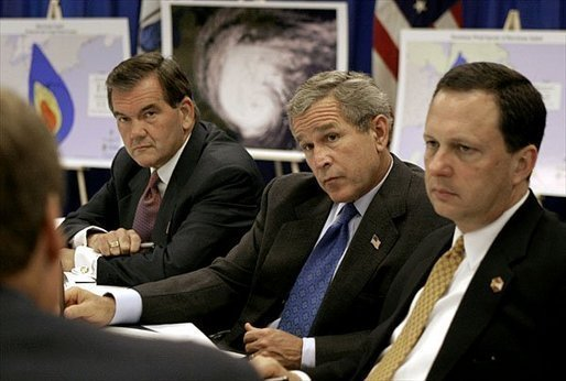 Sitting with Homeland Security Secretary Tom Ridge, left, and Under Secretary Mike Brown of FEMA, President George W. Bush receives a briefing on the damage inflicted by Hurricane Isabel during a tour of the temporary operations center at the Virginia State Police Academy in Richmond, Va., Monday, Sept. 22, 2003. White House photo by Paul Morse.