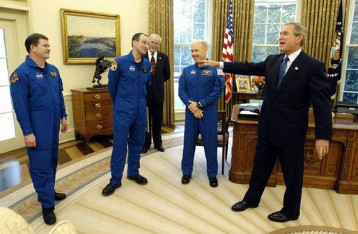 President George W. Bush shares a laugh with members of the International Space Station Expedition 6 Crew during their photo opportunity in the Oval Office Wednesday, Oct. 1, 2003. From left, are, Russian Flight Engineer Nikolai Budarin, Science Officer Donald Pettit, and Commander Kenneth Bowersox. Also pictured in background is NASA Administrator Sean O'Keefe. White House photo by Eric Draper.