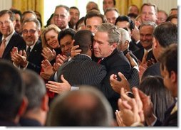 President George W. Bush embraces Brazilian Musician Alexandre Pires after his performance during the Celebration of Hispanic Heritage Month in the East Room, Thursday, Oct 2, 2003.  White House photo by Tina Hager