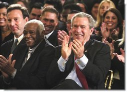 President George W. Bush applauds during the Celebration of Hispanic Heritage Month in the East Room, Thursday, Oct 2, 2003. Also pictured from left are, Tony Garza, U.S. Ambassador to Mexico and Pedro Knight, the husband of late singer Celia Cruz.  White House photo by Eric Draper