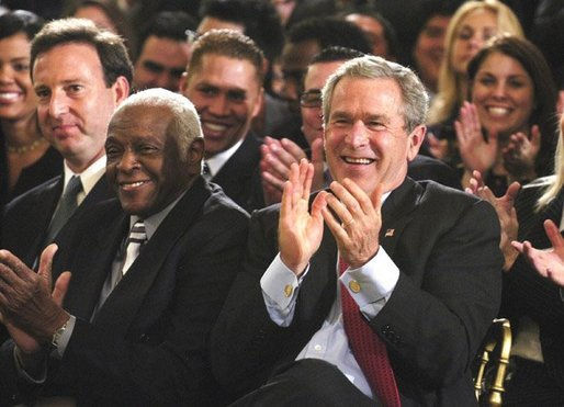President George W. Bush applauds during the Celebration of Hispanic Heritage Month in the East Room, Thursday, Oct 2, 2003. Also pictured from left are, Tony Garza, U.S. Ambassador to Mexico and Pedro Knight, the husband of late singer Celia Cruz. White House photo by Eric Draper.