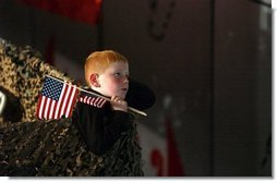 Keeping a grip on his souvenir flags, a boy listens to President George W. Bush at Pease Air National Guard Base in Portsmouth, N.H., Thursday, Oct. 9, 2003.  White House photo by Tina Hager