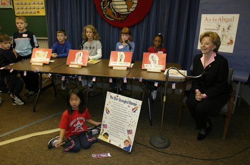 "Lynne Cheney appears as the special guest on WKID, a live televised morning news program for and by Ashurst Elementary School students, on Marine Corps Base, Quantico, Va., Oct. 23, 2003. After singing the Star-Spangled Banner, Mrs. Cheney discussed her two children's books ""America: A Patriotic Primer"" and ""A is for Abigail: An Almanac of Amazing American Women"" during the segment titled The Reading Corner. Pictured are the student anchors for the program who are, from left, Micheal Finney, Alexis Till, Breena McCarthy and Amber Warford. White House photo by David Bohrer."
