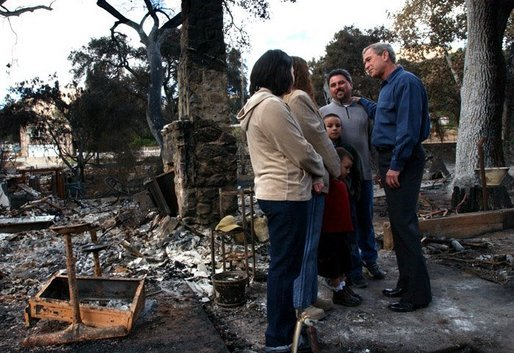 President George W. Bush meets with the Bentley family during a walking tour of the fire-damaged Harbison Canyon community in San Diego, Calif., Tuesday, Nov. 4, 2003. The Bentley family lost their home in last week's wildfires. White House photo by Eric Draper.