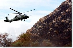 Flying aboard Marine One, President George W. Bush lands in Harbison Canyon after an aerial tour of fire damage in the San Diego, Calif., Tuesday, Nov. 4, 2003.  White House photo by Eric Draper