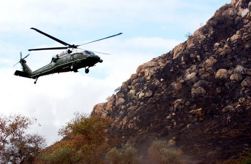 Flying aboard Marine One, President George W. Bush lands in Harbison Canyon after an aerial tour of fire damage in the San Diego, Calif., Tuesday, Nov. 4, 2003. White House photo by Eric Draper.